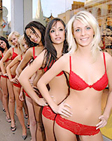 Wearing only red laced bra and panties these group of girls model in the window of a store.